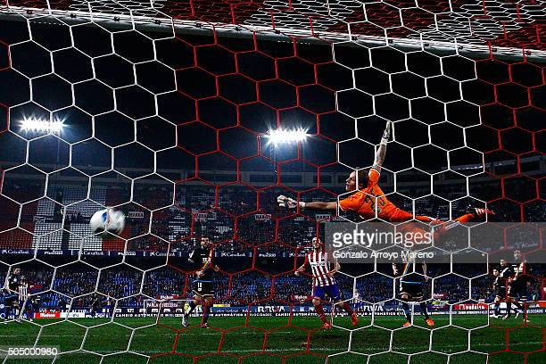 Angel Martin Correa of Atletico de Madrid scores their opening goal against goalkeeper Yoel Rodriguez of Rayo Vallecano de Madrid during the Copa del...