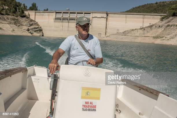 Angel Martinez who has been working as a pier staff at Entrepenas reservoir for 33 years sails with the dam of Entrepenas reservoir on the background...