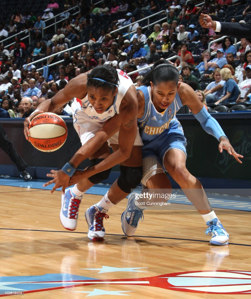 Angel McCoughtry of the Atlanta Dream battles for a loose ball against Tamera Young of the Chicago Sky at Philips Arena on July 3 2010 in Atlanta...
