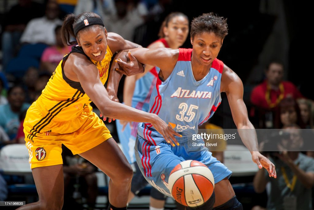Angel McCoughtry #35 of the Atlanta Dream dives for a loose ball against Candice Wiggins #2 of the Tulsa Shock during the WNBA game on July 21, 2013 at the BOK Center in Tulsa, Oklahoma.