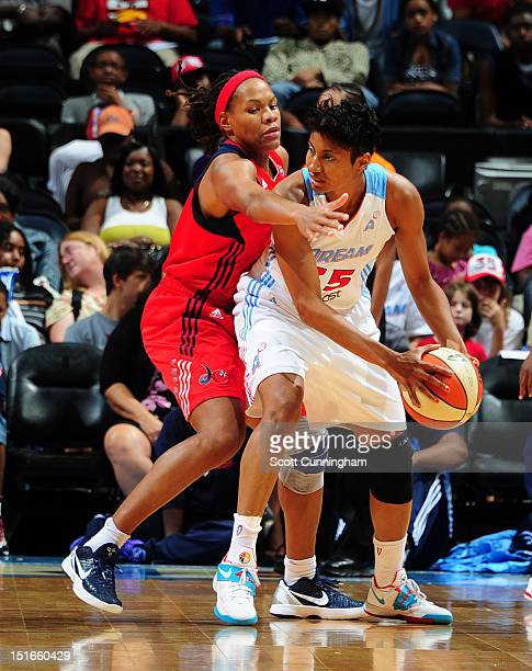 Angel McCoughtry of the Atlanta Dream looks to pass against Monique Currie of the Washington Mystics at Philips Arena on September 9 2012 in Atlanta...