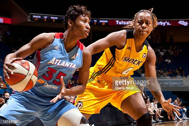 Angel McCoughtry of the Atlanta Dream moves the ball against Amber Holt of the Tulsa Shock during the WNBA game on June 29 2012 at the BOK Center in...