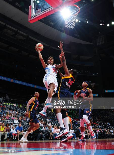 Angel McCoughtry of the Atlanta Dream puts up a shot against Jessica Davenport of the Indiana Fever at Philips Arena on June 26 2012 in Atlanta...