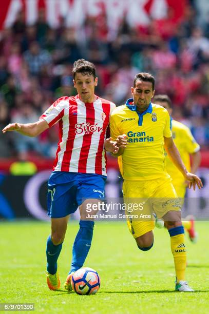 Angel Montoro of UD Las Palmas duels for the ball with Mikel Vesga of Real Sporting de Gijon during the La Liga match between Real Sporting de Gijon...