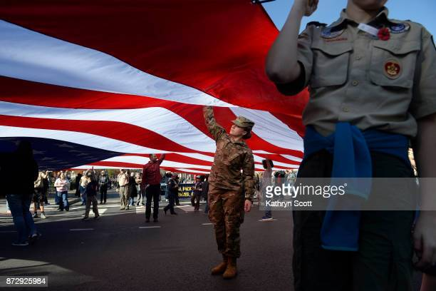Angel Motisi who serves in the Army military police force helps to carry a large American flag honoring Denver's VFW Post 1 and other organizations...
