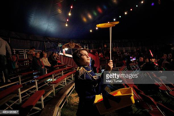 Angel Nicols aged 12 spins plates as the crowd begin to enter the Big Top tent for the first Mr Fips' Wonder Circus show of the day on April 7 2014...