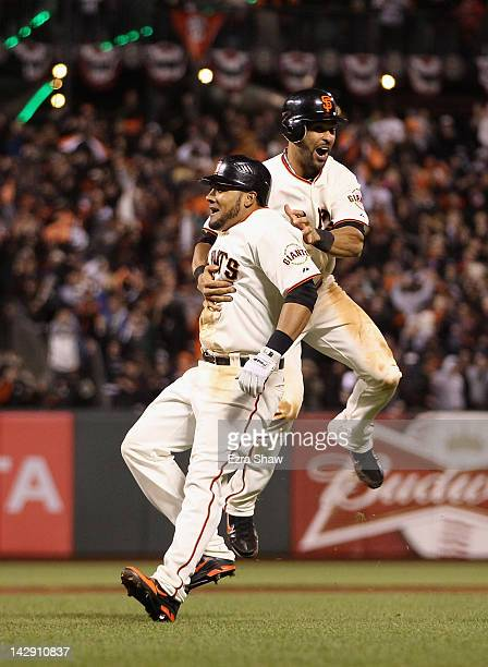 Angel Pagan celebrates with Melky Cabrera of the San Francisco Giants after Cabrera hit a fielders choice in the ninth inning to score Emmanuel...