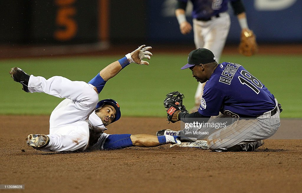 Angel Pagan of the New York Mets is tagged out by Jonathan Herrera of the Colorado Rockies trying to run out a double in the sixth inning on April 11...