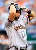 Angel Pagan of the San Francisco Giants adjusts his helmet prior to batting during the game against the Kansas City Royals at Kauffman Stadium on...