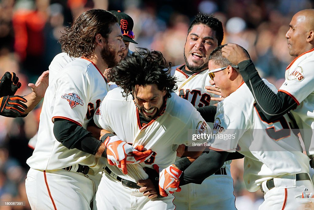 <a gi-track='captionPersonalityLinkClicked' href=/galleries/search?phrase=Angel+Pagan&family=editorial&specificpeople=666596 ng-click='$event.stopPropagation()'>Angel Pagan</a> #16 of the San Francisco Giants gets swarmed by his team after he hit a walk-off single to score Ehire Adrianza #53 against the Arizona Diamondbacks in the 11th inning at AT&T Park on September 8, 2013 in San Francisco, California. The Giants won 3-2 in 11 innnings.
