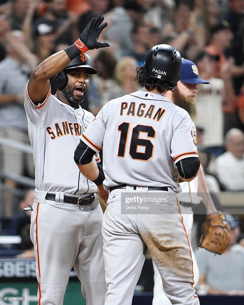 Angel Pagan #16 of the San Francisco Giants, right, is congratulated by Denard Span #2 after he scored during the tenth inning of a baseball game against the San Diego Padres at PETCO Park on September 24, 2016 in San Diego, California.