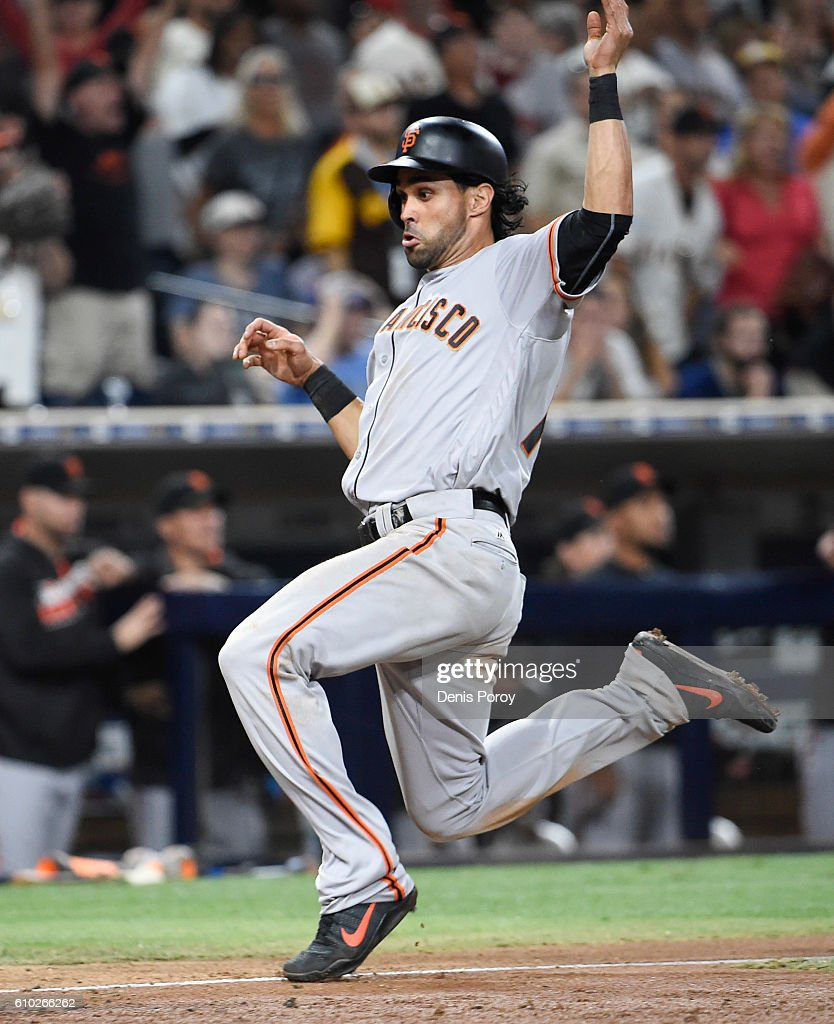 Angel Pagan #16 of the San Francisco Giants slides as he scores during the tenth inning of a baseball game against the San Diego Padres at PETCO Park on September 24, 2016 in San Diego, California.