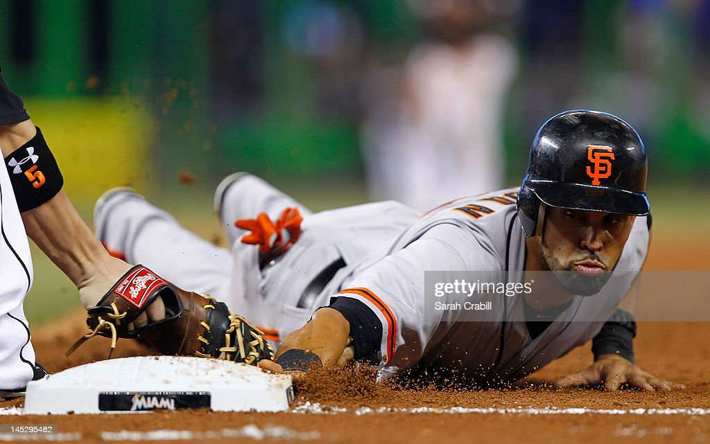 <a gi-track='captionPersonalityLinkClicked' href=/galleries/search?phrase=Angel+Pagan&family=editorial&specificpeople=666596 ng-click='$event.stopPropagation()'>Angel Pagan</a> #16 of the San Francisco Giants slides safely back to first base before the tag of Logan Morrison #5 of the Miami Marlins during a game at Marlins Park on May 25, 2012 in Miami, Florida.