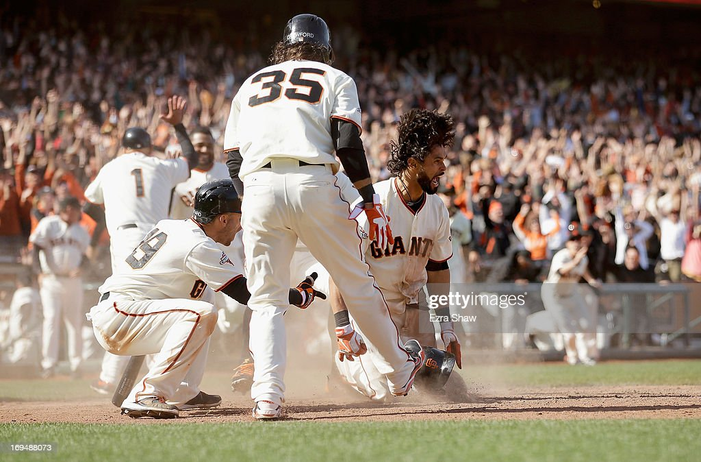 Angel Pagen #16 of the San Francisco Giants reacts after he slide in to home plate for a walk-off inside-the-park home run to beat the Colorado Rockies in ten innings at AT&T Park on May 25, 2013 in San Francisco, California.