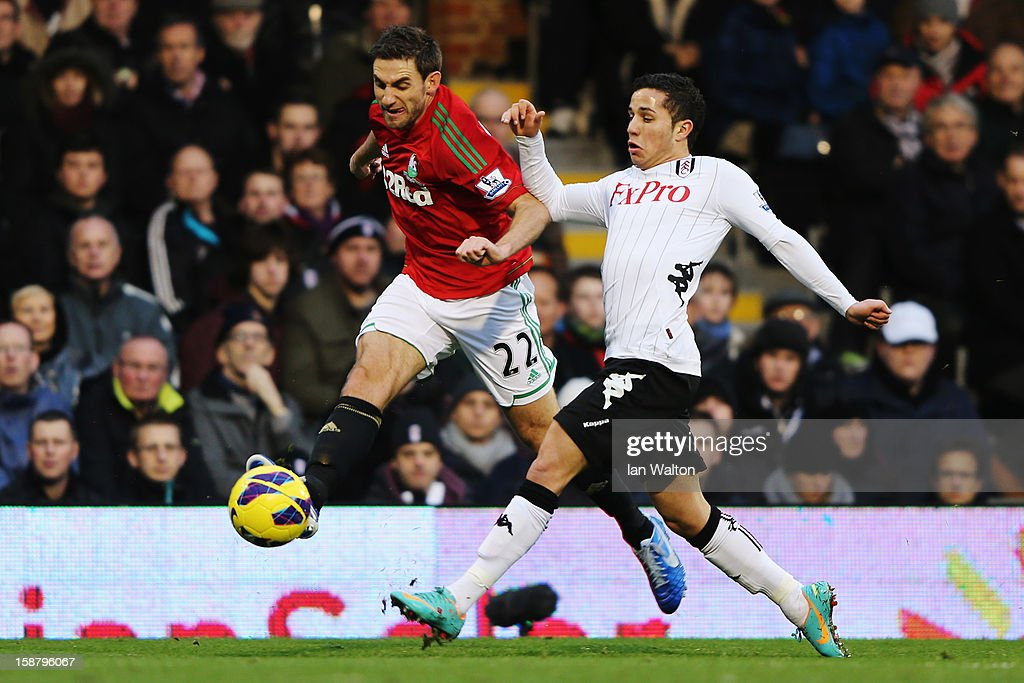 Angel Rangel (L) of Swansea City and Kerim Frei of Fulham challenge for the ball during the Barclays Premier League match between Fulham and Swansea City at Craven Cottage on December 29, 2012 in London, England.