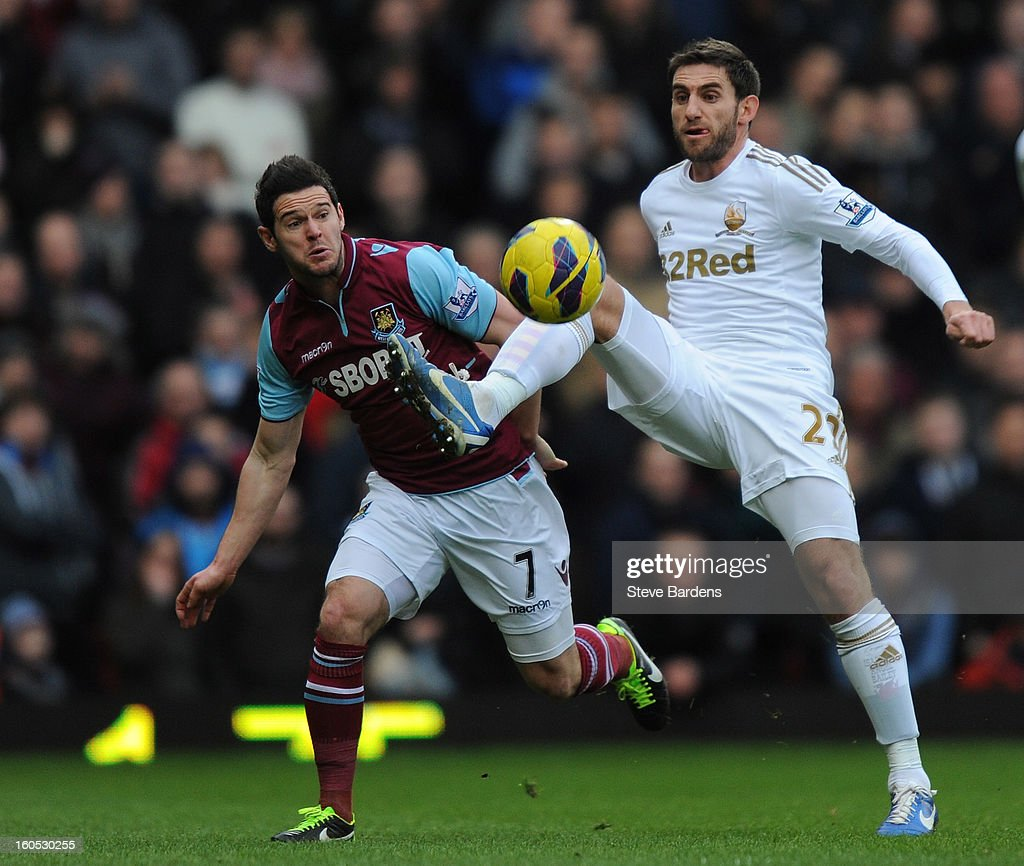 Angel Rangel of Swansea City holds off the challenge of Matt Jarvis of West Ham United during the Barclays Premier League match between West Ham United and Swansea at the Boleyn Ground on February 2, 2013 in London, England.