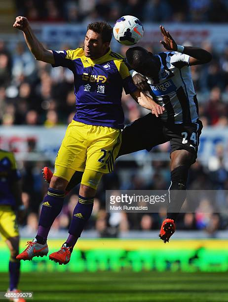 Angel Rangel of Swansea City jumps with Cheik Ismael Tiote of Newcastle United during the Barclays Premier League match between Newcastle United and...