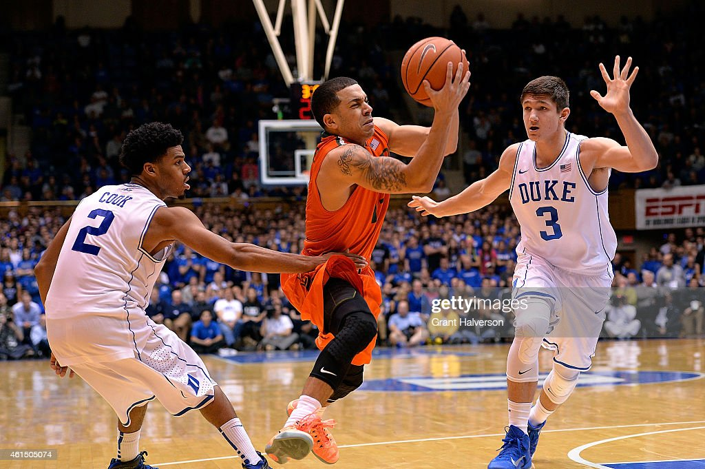 Angel Rodriguez of the Miami Hurricanes drives between Quinn Cook and Grayson Allen of the Duke Blue Devils during their game at Cameron Indoor...