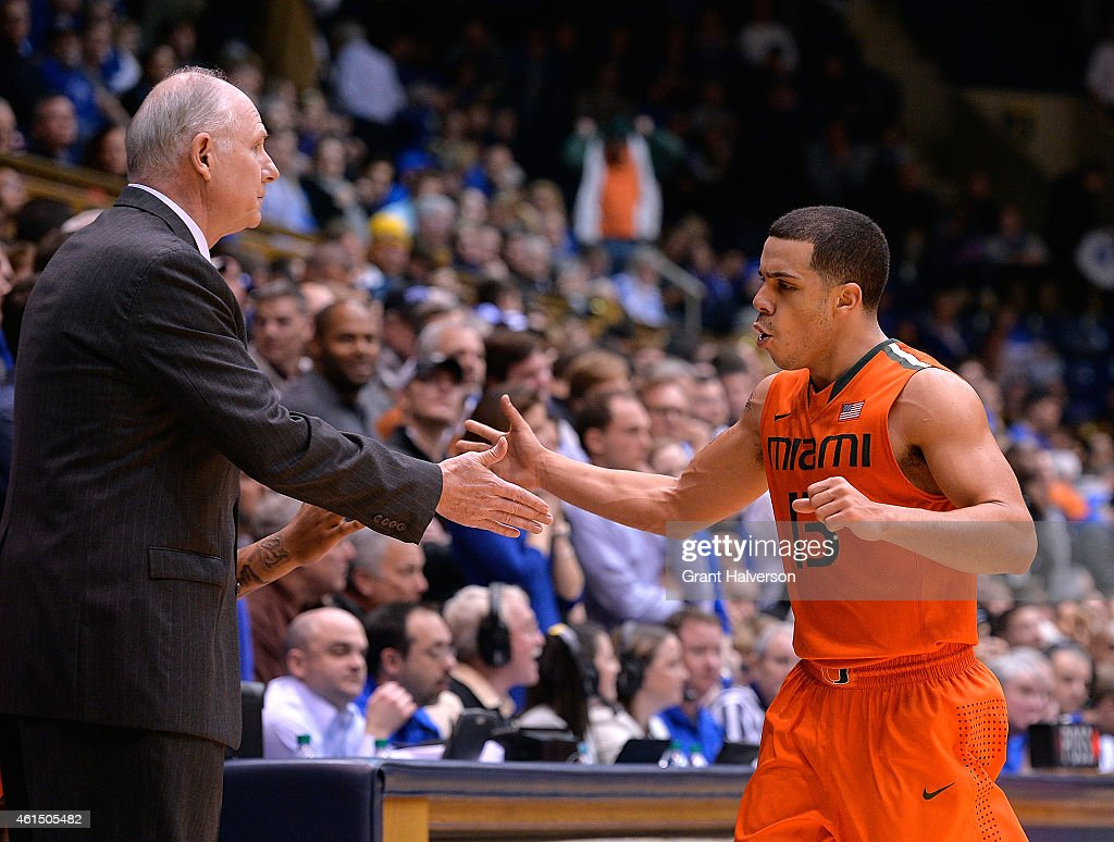 Angel Rodriguez of the Miami Hurricanes highfives head coach Jim Larranaga of the Miami Hurricanes as he leaves the floor during the final seconds of...