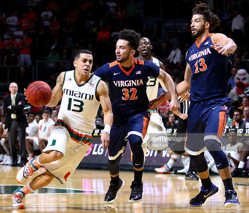 Angel Rodriguez of the Miami Hurricanes in action against London Perrantes and Anthony Gill of the Virginia Cavaliers during the game at the...
