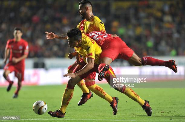 Angel Sepulveda and Mario Osuna of Morelia vies for the ball with Pedro Canelo of Toluca during their querter final Mexican Apertura tournament...