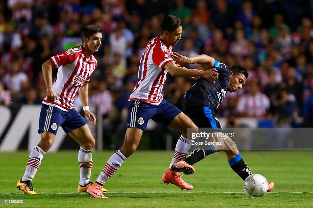 Angel Sepulveda of Queretaro struggles for the ball with Edwin Hernandez of Chivas during the 9th round match between Queretaro and Chivas as part of the Clausura 2016 Liga MX at La Corregidora Stadium on March 05, 2016 in Queretaro, Mexico.
