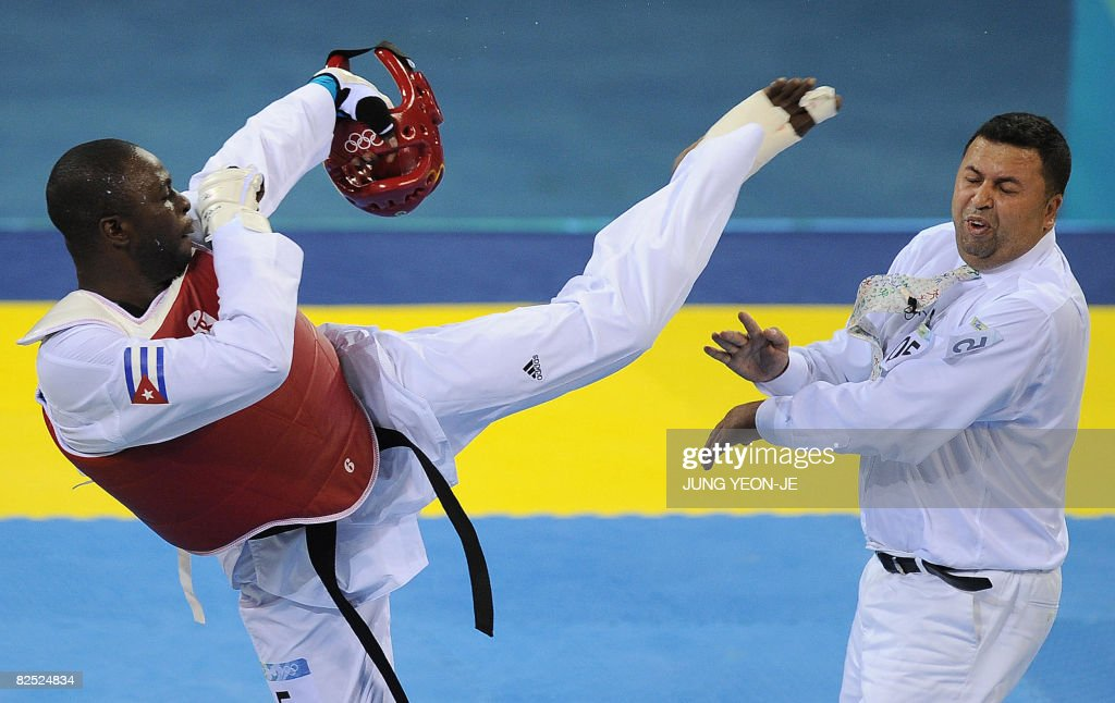 Angel Valodia Matos (L-red) of Cuba lands a kick on the face of referee Chakir Chelbat (R) of Sweden after he lost his bronze medal contest in the men's +80 kg taekwondo competition against Arman Chilmanov of Kazakhstan during the 2008 Beijing Olympic Games in Beijing on August 23, 2008. Cuba's former Olympic taekwondo champion Angel Valodia Matos was expelled from major international competitions for kicking the referee in the head when he was disqualified in the match.