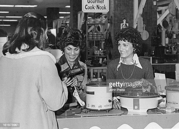 MAY 14 1975 Angela Grandinetti Shows a Mark III Curling Iron to Prospective Customer Mary Grandinetti stands by to demonstrate the Crockery Casserole...