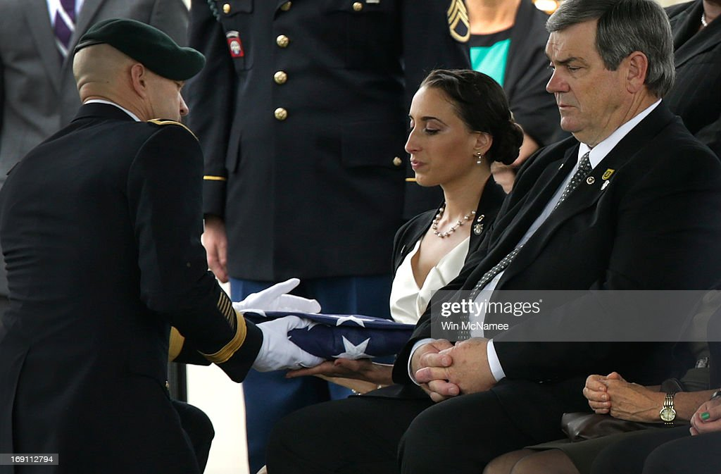 Angela Grissom (C) receives an American flag from Brigadier Gen. Darsie Rogers (L) during a burial service for her husband Sergeant First Class James F. Grissom at Arlington National Cemetery May 20, 2013 in Arlington, Virginia. Also pictured is Grissom's father, James Grissom. Grissom, from Hayward, California, died from wounds suffered in combat in Paktika province, Afghanistan.