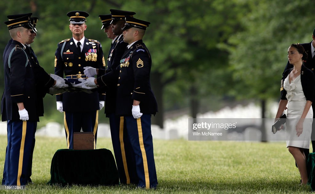Angela Grissom (R) watches as an Army burial team prepares for a burial service for her husband Sergeant First Class James F. Grissom at Arlington National Cemetery May 20, 2013 in Arlington, Virginia. Grissom, from Hayward, California, died from wounds suffered in combat in Paktika province, Afghanistan.