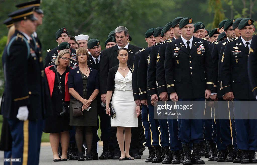 Angela Grissom (C) watches as an U.S. Army burial team prepares for a burial service for her husband Sergeant First Class James F. Grissom at Arlington National Cemetery May 20, 2013 in Arlington, Virginia. Grissom, from Hayward, California, died from wounds suffered in combat in Paktika province, Afghanistan.