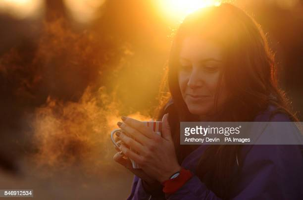 Angela Lurssen holds a hot drink before she braved the early morning cold weather in the Serpentine in Hyde Park London as parts of Britain were...