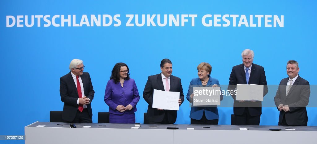 Angela Merkel, Chancellor and Chairwoman of the German Christian Democrats (CDU), <a gi-track='captionPersonalityLinkClicked' href=/galleries/search?phrase=Horst+Seehofer&family=editorial&specificpeople=4273631 ng-click='$event.stopPropagation()'>Horst Seehofer</a> (R), Chairman of the Bavarian Christian Democrats (CSU) and <a gi-track='captionPersonalityLinkClicked' href=/galleries/search?phrase=Sigmar+Gabriel&family=editorial&specificpeople=543927 ng-click='$event.stopPropagation()'>Sigmar Gabriel</a>, Chairman of the German Social Democrats (SPD), pose after signing the coalition agreement between the three parties that seals their cooperation and allows the creation of a new German coalition government as new cabinet members (from L to R) Foreign Minister <a gi-track='captionPersonalityLinkClicked' href=/galleries/search?phrase=Frank-Walter+Steinmeier&family=editorial&specificpeople=603500 ng-click='$event.stopPropagation()'>Frank-Walter Steinmeier</a>, Minister of Work and Social Issues <a gi-track='captionPersonalityLinkClicked' href=/galleries/search?phrase=Andrea+Nahles&family=editorial&specificpeople=822618 ng-click='$event.stopPropagation()'>Andrea Nahles</a> and Health Minister Hermann Groehe look on under a slogan that reads: 'Creating Germany's Future' on December 16, 2013 in Berlin, Germany. The new government is scheduled to be sworn in tomorrow.