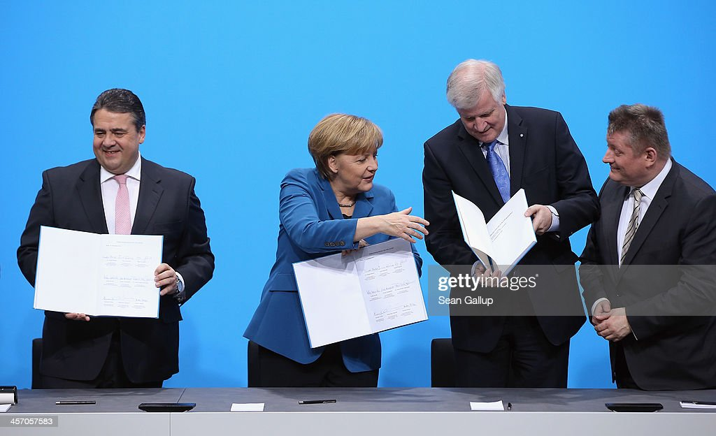 Angela Merkel, Chancellor and Chairwoman of the German Christian Democrats (CDU), <a gi-track='captionPersonalityLinkClicked' href=/galleries/search?phrase=Horst+Seehofer&family=editorial&specificpeople=4273631 ng-click='$event.stopPropagation()'>Horst Seehofer</a> (2nd from R), Chairman of the Bavarian Christian Democrats (CSU) and <a gi-track='captionPersonalityLinkClicked' href=/galleries/search?phrase=Sigmar+Gabriel&family=editorial&specificpeople=543927 ng-click='$event.stopPropagation()'>Sigmar Gabriel</a>, Chairman of the German Social Democrats (SPD), prepare to pose after signing the coalition agreement between the three parties that seals their cooperation and allows the creation of a new German coalition government as new cabinet member Health Minister Hermann Groehe (R) looks on on December 16, 2013 in Berlin, Germany. The new government is scheduled to be sworn in tomorrow.