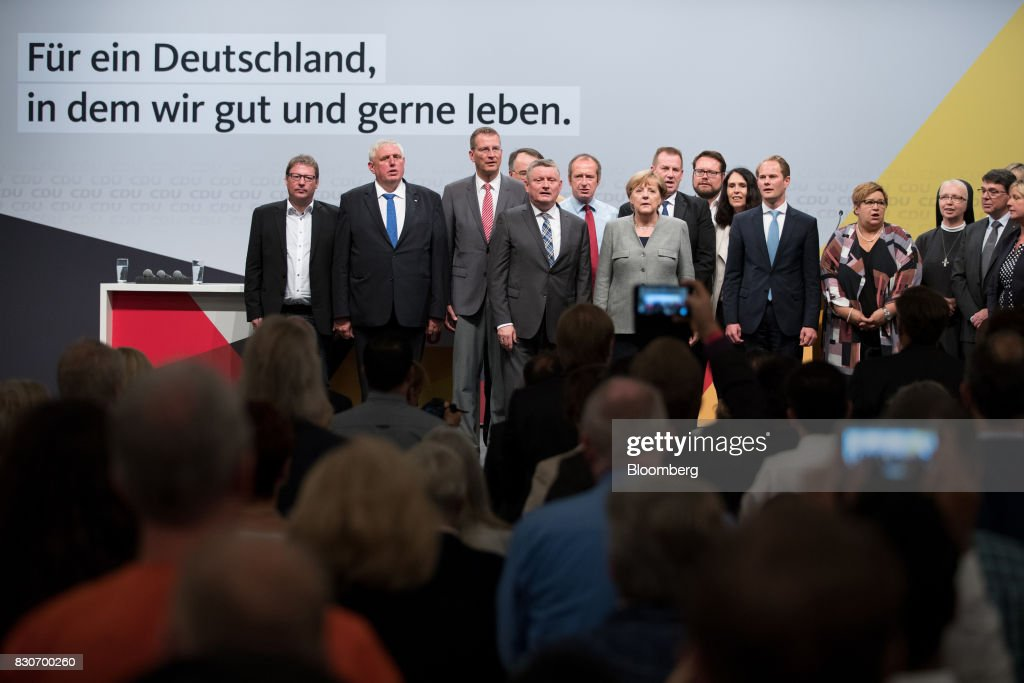 Angela Merkel, Germany's chancellor and Christian Democratic Union (CDU) leader, center, sings the national anthem with party members after speaking during a campaign event in Dortmund, Germany, on Saturday, Aug. 12, 2017. Merkelopened her re-election campaign with criticism of the nations auto executives, saying they need to embrace new technology more quickly to protect jobs and repair damage done by adiesel cheating scandal. Photographer: Jasper Juinen/Bloomberg via Getty Images