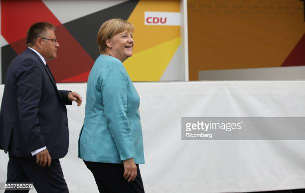 Angela Merkel Germany's chancellor and Christian Democratic Union leader right smiles as she walks off stage during an election campaign stop in...