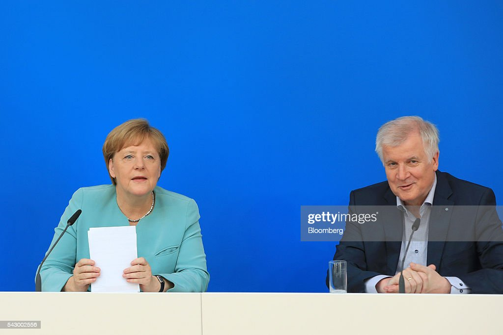 Angela Merkel, Germany's chancellor and leader of the Christian Democratic Union (CDU) party, left, and Horst Seehofer, Bavarian premier and leader of the Christian Social Union (CSU) party, react during a news conference in Potsdam, Germany, on Saturday, June 25, 2016. Merkel signaled she wants to avoid punishing the U.K. as it leaves the European Union, though the exit talks shouldnt drag on forever. Photographer: Krisztian Bocsi/Bloomberg via Getty Images