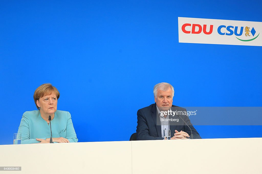 Angela Merkel, Germany's chancellor and leader of the Christian Democratic Union (CDU) party, left, listens as Horst Seehofer, Bavarian premier and leader of the Christian Social Union (CSU) party, speaks during a news conference in Potsdam, Germany, on Saturday, June 25, 2016. Merkel signaled she wants to avoid punishing the U.K. as it leaves the European Union, though the exit talks shouldnt drag on forever. Photographer: Krisztian Bocsi/Bloomberg via Getty Images