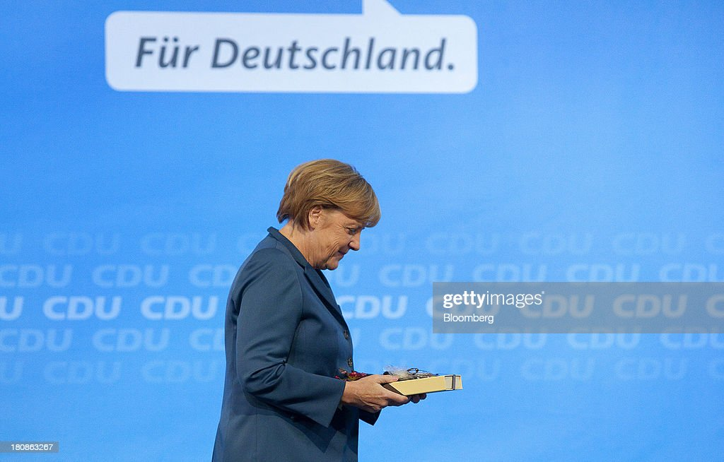 <a gi-track='captionPersonalityLinkClicked' href=/galleries/search?phrase=Angela+Merkel&family=editorial&specificpeople=202161 ng-click='$event.stopPropagation()'>Angela Merkel</a>, Germany's chancellor and party leader of the Christian Democratic Union (CDU), holds a gift box of chocolates as she leaves the stage following her speech during an election rally in Potsdam, Germany, on Monday, Sept. 16, 2013. Delayed plans for a financial transaction tax in 11 European states would get a fresh push if Chancellor <a gi-track='captionPersonalityLinkClicked' href=/galleries/search?phrase=Angela+Merkel&family=editorial&specificpeople=202161 ng-click='$event.stopPropagation()'>Angela Merkel</a> enters a coalition with the Social Democrats after Sept. 22 German elections, top SPD members said. Photographer: Krisztian Bocsi/Bloomberg via Getty Images