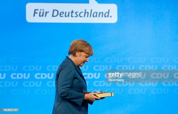 Angela Merkel Germany's chancellor and party leader of the Christian Democratic Union holds a gift box of chocolates as she leaves the stage...