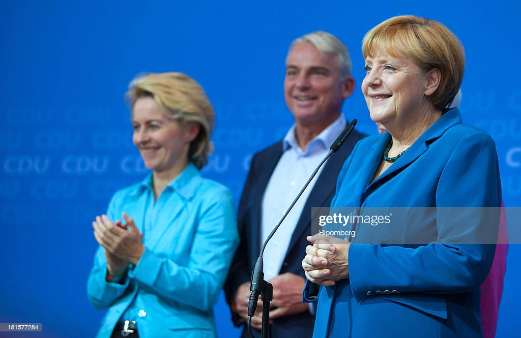 Angela Merkel, Germany's chancellor and party leader of the Christian Democratic Union (CDU), right, stands next to Ursula von der Leyen, Federal Minister of Labour, left, and Thomas Strobl, Baden-Württemberg state CDU party chairman, center, before a speech by Merkel at the CDU headquarters as the German federal elections result is announced in Berlin, Germany, on Sunday, Sept. 22, 2013. Merkel won an overwhelming endorsement from German voters, putting the country's first female chancellor on course for the biggest election tally since Helmut Kohl's post-reunification victory of 1990. Photographer: Krisztian Bocsi/Bloomberg via Getty Images