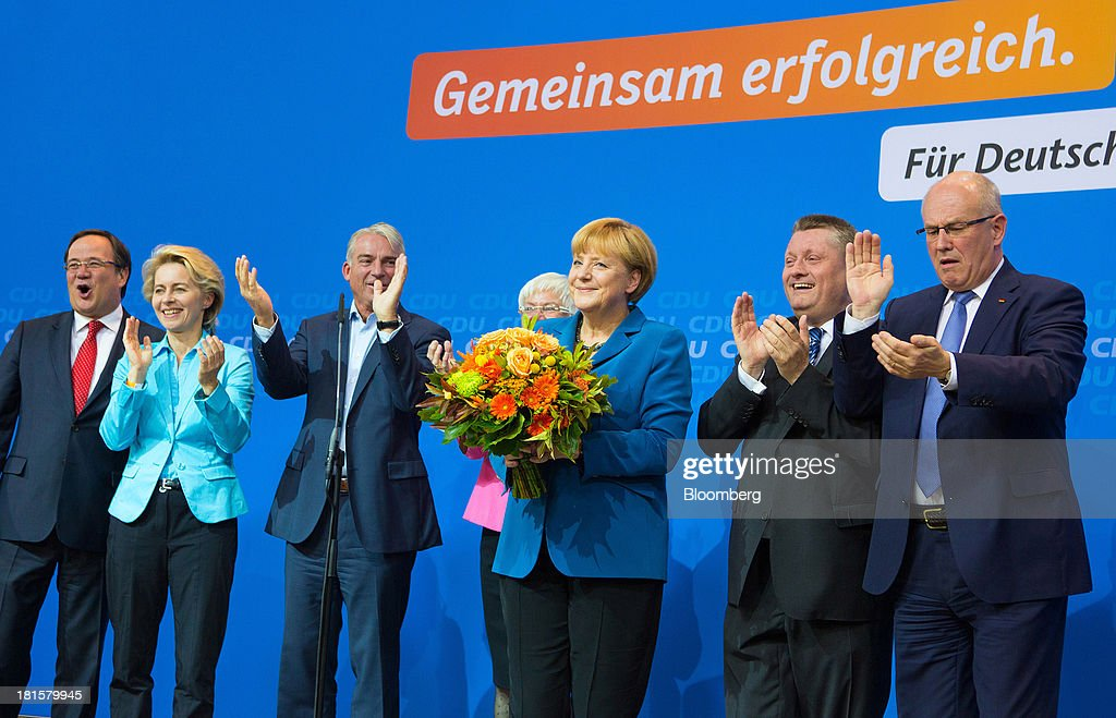 <a gi-track='captionPersonalityLinkClicked' href=/galleries/search?phrase=Angela+Merkel&family=editorial&specificpeople=202161 ng-click='$event.stopPropagation()'>Angela Merkel</a>, Germany's chancellor and party leader of the Christian Democratic Union (CDU), stands holding flowers next to Armin Laschet, CDU regional party chairman, left, <a gi-track='captionPersonalityLinkClicked' href=/galleries/search?phrase=Ursula+von+der+Leyen&family=editorial&specificpeople=4249207 ng-click='$event.stopPropagation()'>Ursula von der Leyen</a>, Federal Minister of Labour, second from left, Thomas Strobl, Baden-Württemberg state CDU party chairman, third from left, Gerda Hasselfeldt, head of the Christian Social Union, center rear, Hermann Gröhe, CDU secretary general, second from right, and Volke Kauder, parliamentary floor leader of the CDU, at the CDU headquarters as the German federal elections result is announced in Berlin, Germany, on Sunday, Sept. 22, 2013. Merkel won an overwhelming endorsement from German voters, putting the country's first female chancellor on course for the biggest election tally since Helmut Kohl's post-reunification victory of 1990. Photographer: Krisztian Bocsi/Bloomberg via Getty Images