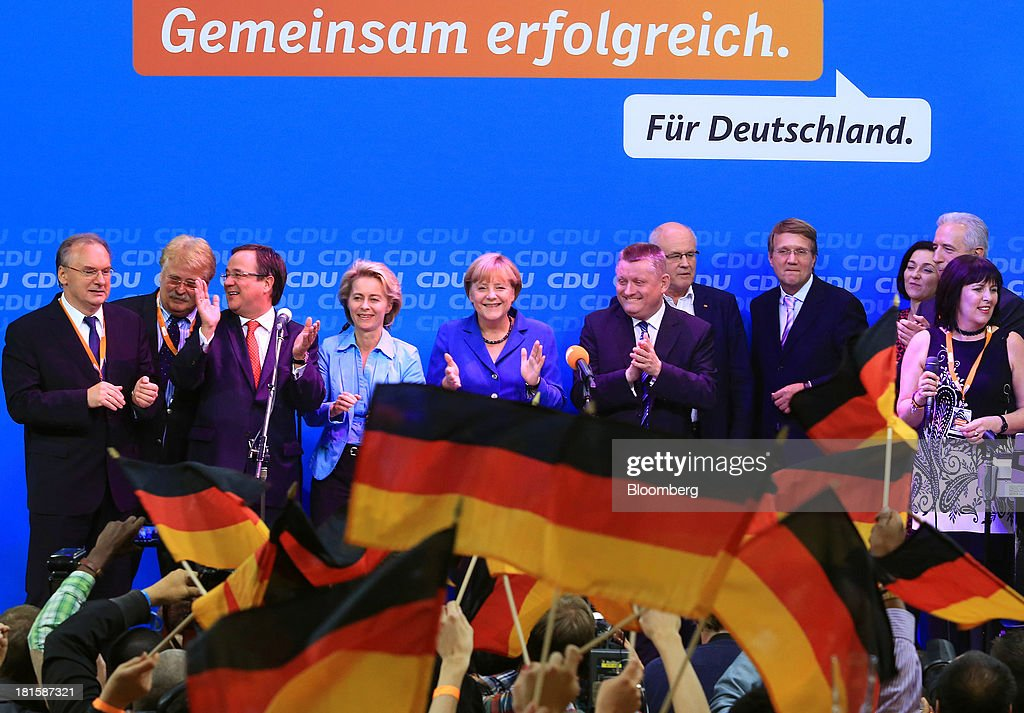 Angela Merkel, Germany's chancellor and party leader of the Christian Democratic Union (CDU), center, stands with supporters on stage during victory celebrations at the CDU headquarters after the German federal elections results were announced in Berlin, Germany, on Sunday, Sept. 22, 2013. Merkel won an overwhelming endorsement from German voters, putting the country's first female chancellor on course for the biggest election tally since Helmut Kohl's post-reunification victory of 1990. Photographer: Krisztian Bocsi/Bloomberg via Getty Images