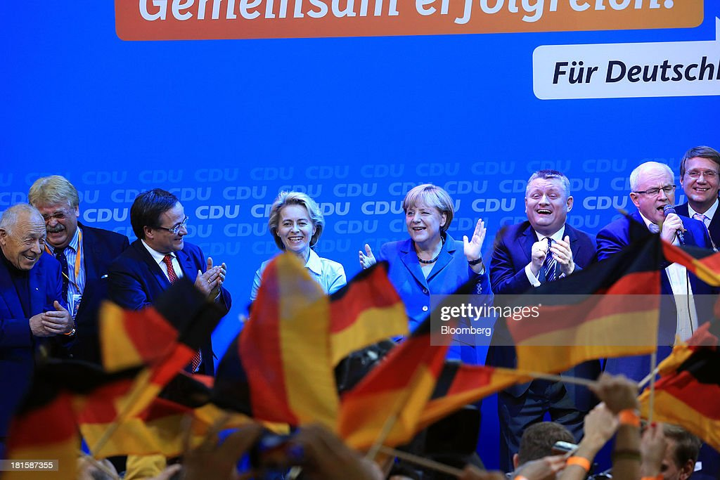 <a gi-track='captionPersonalityLinkClicked' href=/galleries/search?phrase=Angela+Merkel&family=editorial&specificpeople=202161 ng-click='$event.stopPropagation()'>Angela Merkel</a>, Germany's chancellor and party leader of the Christian Democratic Union (CDU), center, stands with supporters on stage during victory celebrations at the CDU headquarters after the German federal elections results were announced in Berlin, Germany, on Sunday, Sept. 22, 2013. Merkel won an overwhelming endorsement from German voters, putting the country's first female chancellor on course for the biggest election tally since Helmut Kohl's post-reunification victory of 1990. Photographer: Krisztian Bocsi/Bloomberg via Getty Images