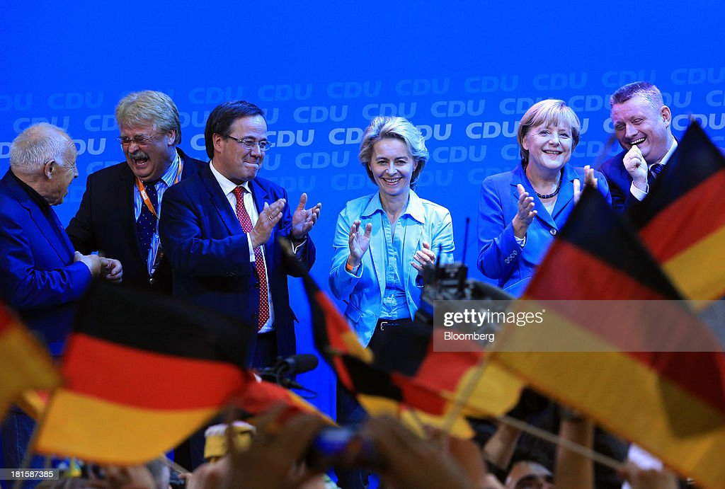 Angela Merkel, Germany's chancellor and party leader of the Christian Democratic Union (CDU), second from right, stands with supporters on stage during victory celebrations at the CDU headquarters after the German federal elections results were announced in Berlin, Germany, on Sunday, Sept. 22, 2013. Merkel won an overwhelming endorsement from German voters, putting the country's first female chancellor on course for the biggest election tally since Helmut Kohl's post-reunification victory of 1990. Photographer: Krisztian Bocsi/Bloomberg via Getty Images
