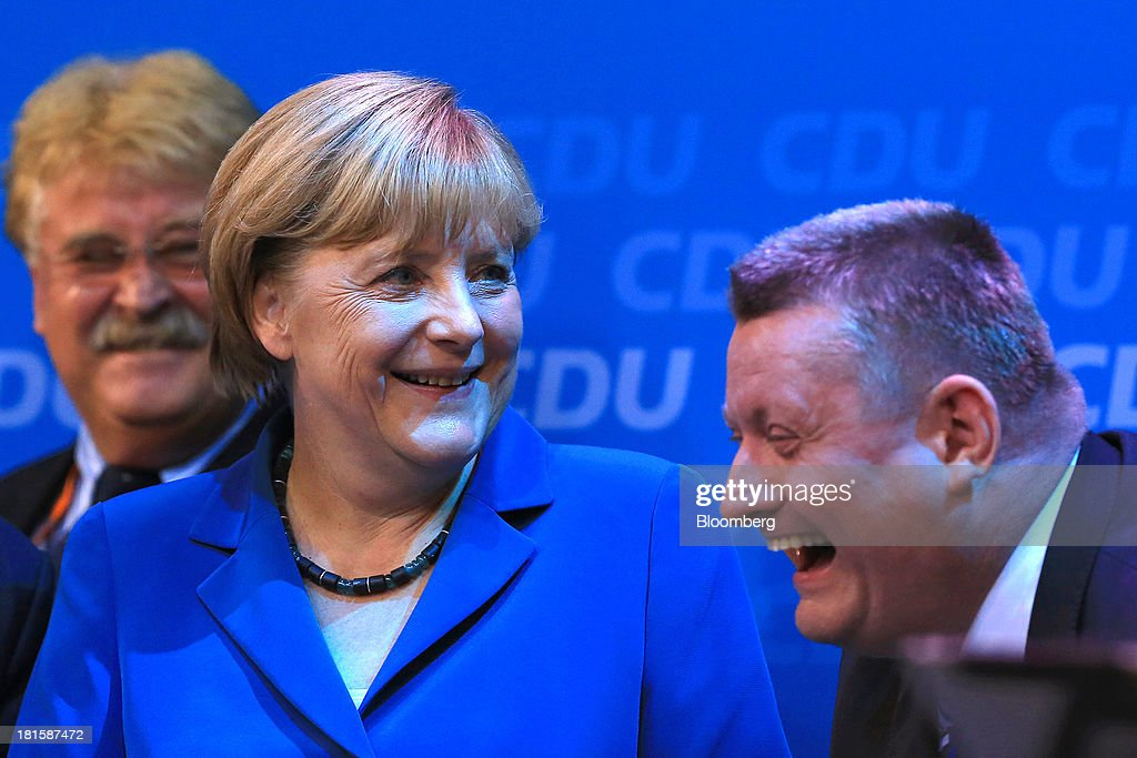 Angela Merkel, Germany's chancellor and party leader of the Christian Democratic Union (CDU), smiles next to Hermann Gröhe, CDU secretary general, right, during victory celebrations at the CDU headquarters after the German federal elections results were announced in Berlin, Germany, on Sunday, Sept. 22, 2013. Merkel won an overwhelming endorsement from German voters, putting the country's first female chancellor on course for the biggest election tally since Helmut Kohl's post-reunification victory of 1990. Photographer: Krisztian Bocsi/Bloomberg via Getty Images