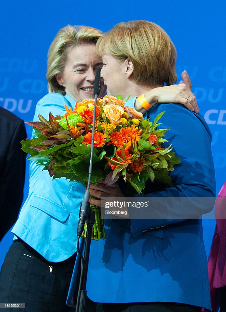 Angela Merkel, Germany's chancellor and party leader of the Christian Democratic Union (CDU), right, is embraced by Ursula von der Leyen, Germany's labor minister, on stage during victory celebrations at the CDU headquarters after the German federal elections results were announced in Berlin, Germany, on Sunday, Sept. 22, 2013. Merkel won an overwhelming endorsement from German voters, putting the country's first female chancellor on course for the biggest election tally since Helmut Kohl's post-reunification victory of 1990. Photographer: Krisztian Bocsi/Bloomberg via Getty Images