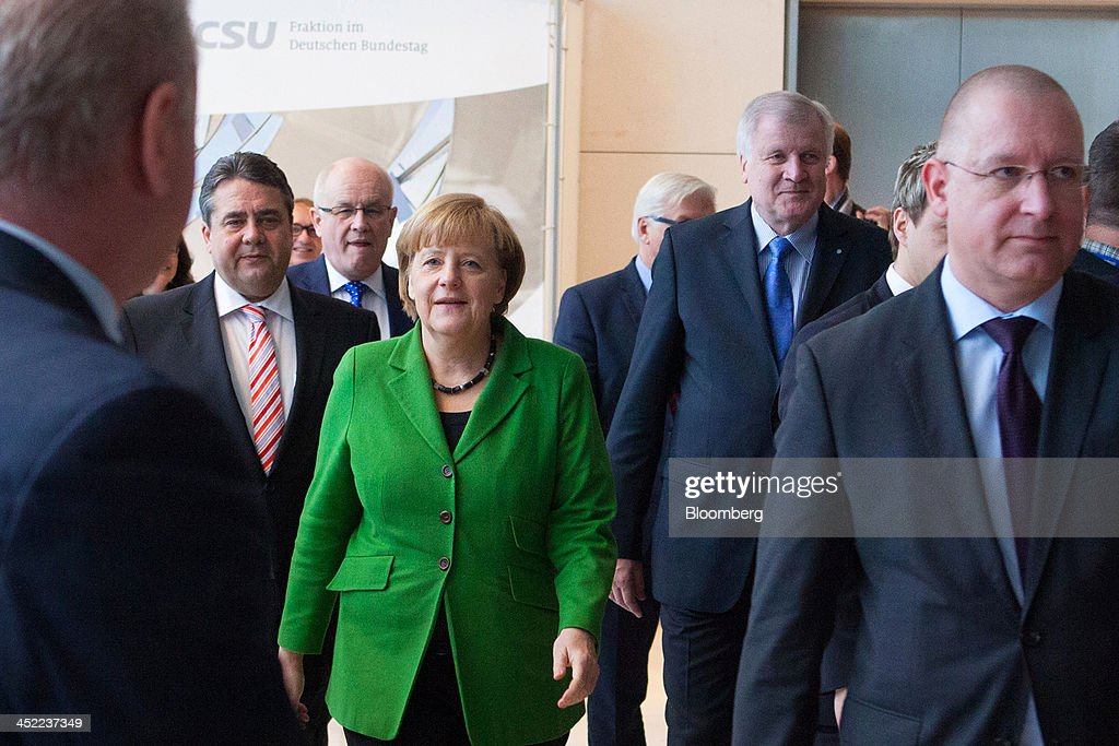 <a gi-track='captionPersonalityLinkClicked' href=/galleries/search?phrase=Angela+Merkel&family=editorial&specificpeople=202161 ng-click='$event.stopPropagation()'>Angela Merkel</a>, Germany's chancellor, center, arrives at the German parliament building, or Reichstag, with <a gi-track='captionPersonalityLinkClicked' href=/galleries/search?phrase=Sigmar+Gabriel&family=editorial&specificpeople=543927 ng-click='$event.stopPropagation()'>Sigmar Gabriel</a>, head of the Social Democratic Party (SPD), second left, and <a gi-track='captionPersonalityLinkClicked' href=/galleries/search?phrase=Horst+Seehofer&family=editorial&specificpeople=4273631 ng-click='$event.stopPropagation()'>Horst Seehofer</a>, who heads Merkel's Christian Social Union (CSU) Bavarian sister party, third right, in Berlin, Germany, on Wednesday, Nov. 27, 2013. Merkel reached an agreement with the Social Democrats on a coalition that would implement a national minimum wage and increase spending on pensions and infrastructure without raising taxes. Photographer: Krisztian Bocsi/Bloomberg via Getty Images