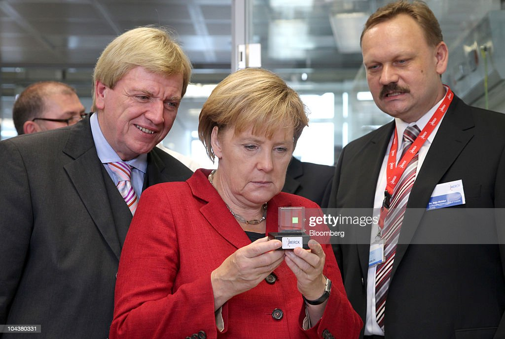 <a gi-track='captionPersonalityLinkClicked' href=/galleries/search?phrase=Angela+Merkel&family=editorial&specificpeople=202161 ng-click='$event.stopPropagation()'>Angela Merkel</a>, Germany's chancellor, center, holds an organic light-emitting diode (OLED) as <a gi-track='captionPersonalityLinkClicked' href=/galleries/search?phrase=Volker+Bouffier&family=editorial&specificpeople=2371294 ng-click='$event.stopPropagation()'>Volker Bouffier</a>, the German state of Hesse's interior minister, left, and Udo Heider, head of the liquid crystals research laboratory at the Merck KGaA research center, looks on in Darmstadt, near Frankfurt, Germany, on Tuesday, Sept. 23, 2010. Merck KGaA is developing liquid crystals for 3-D televisions that don't require special glasses as the company seeks to bolster sales of the fastest-growing use for the product. Photographer: Hannelore Foerster/Bloomberg via Getty Images
