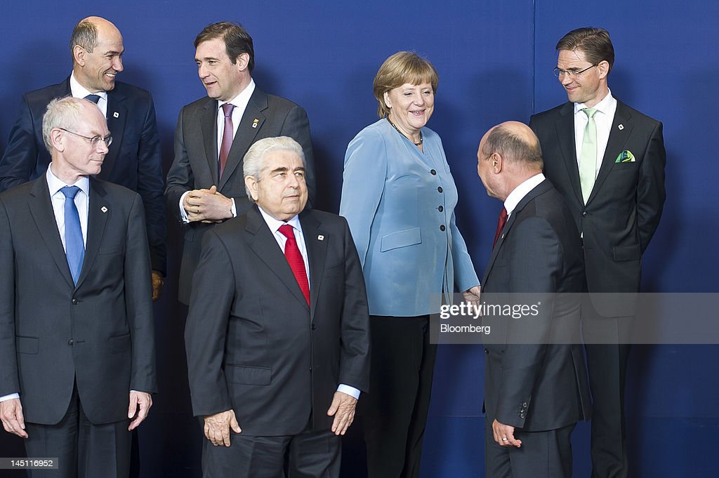 Angela Merkel, Germany's chancellor, center, reacts as she arrives for a family photograph during the European Leaders (EU) summit at the European Council headquarters in Brussels, Belgium, on Wednesday, May 23, 2012. Standing from left back row: <a gi-track='captionPersonalityLinkClicked' href=/galleries/search?phrase=Janez+Jansa&family=editorial&specificpeople=566150 ng-click='$event.stopPropagation()'>Janez Jansa</a>, Slovenia's prime minister, Pedro Passos Coelho, Portugal's prime minister, and <a gi-track='captionPersonalityLinkClicked' href=/galleries/search?phrase=Jyrki+Katainen&family=editorial&specificpeople=3014648 ng-click='$event.stopPropagation()'>Jyrki Katainen</a>, Finland's prime minister, from left front row: <a gi-track='captionPersonalityLinkClicked' href=/galleries/search?phrase=Herman+Van+Rompuy&family=editorial&specificpeople=4476281 ng-click='$event.stopPropagation()'>Herman Van Rompuy</a>, president of the European Council, Dimitris Christofias, president of Cyprus, and <a gi-track='captionPersonalityLinkClicked' href=/galleries/search?phrase=Traian+Basescu&family=editorial&specificpeople=542324 ng-click='$event.stopPropagation()'>Traian Basescu</a>, Romania's president, The summit, the 18th since Greece was convulsed by debt and the first since an anti-austerity campaign carried Hollande to France's presidency, takes place with market indicators showing mounting stress on banks. Photographer: Jock Fistick/Bloomberg via Getty Images